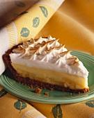 A slice on lemon meringue pie on a green plate