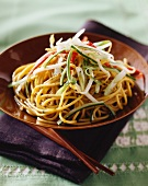 Egg noodles with pepper strips, courgette, sprouts and sesame seed oil (Asia)