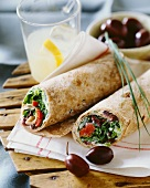 Salad and olive wraps and a glass of lemonade