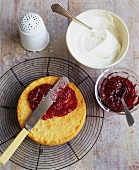 Spreading Strawberry Preserves Over Sponge Cake; Cream