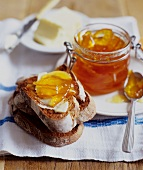 Orange marmalade on bread and in jar