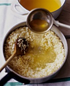 Adding Broth to Arborio Rice for Risotto
