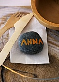 A stone as a place card, serviette and wooden cutlery