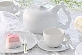 Pink dessert cake on white crockery with festive decoration
