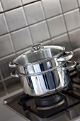 Stainless steel pots stacked on a gas hob