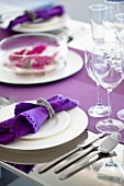 A place setting with a purple napkin in a napkin ring
