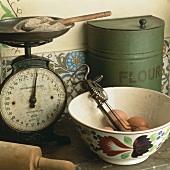 Alte Küchenwaage, Mehldose, Schale mit Eiern & altem Handrührgerät