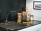 A stainless steel sink with storage jars against a black wall