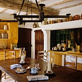 A kitchen in a country house with a wrought iron candle holder above a dark wooden table
