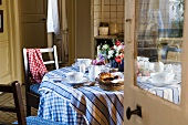 A view through an open door onto a breakfast table in the kitchen of a country house