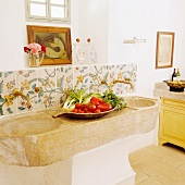 Food being prepared on a rustic stone sink in a kitchen in a Spanish country house