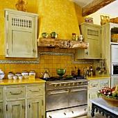 Alte Landhausküche mit kanariengelber Wand und antikem Edelstahlherd mit gemauertem Abzug