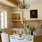 Gedeckter Esstisch und Kristallleuchter in provenzalischer Landhausküche