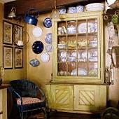 Blauer Korbsessel und Wandteller in der Ecke neben Geschirrschrank