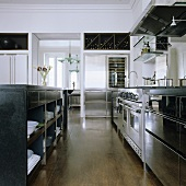An open-plan kitchen with a stainless steel kitchen counter and black cupboards