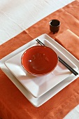 An Oriental place setting with a red bowl on white plates with chopsticks