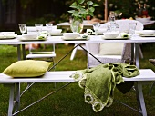 A table laid in a garden with a white bench and green cushions and a blanket