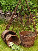 A three piece wicker basket set with fresh garlic in front of a metal trellis