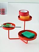 Rotes Metallgestell mit runden Tablett Ablagen und Schreibutensilien