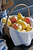 Apples and pears in basket lined with a tea towel