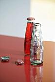 Leere und gefüllte Flasche auf roter Arbeitsplatte
