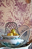 A wire basket over lemons on a ceramic sieve and a stack of plates against a floral-patterned wallpaper