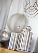 A stainless steel pepper mill and salt shaker