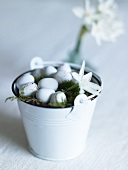 Quail's eggs and moss in a white metal container