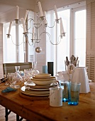 A chandelier with white candles above a wooden table set with crockery