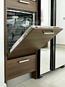 A open, wooden fronted dishwasher