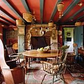 Holztisch mit Windsor-Stühlen und Kamin im Esszimmer eines Landhauses