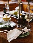 Leinenserviette auf einem Teller, dahinter ein Glas Weißwein