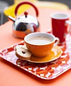 A cup of coffee with a jam biscuit on a tray