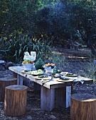 Rustikaler Holztisch und Baumstamm-Hocker in einem ländlichen Garten