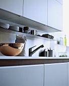 weiße Küchenzeile mit einer Kupferschüssel