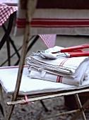 Rot-weisse Geschirrtücher mit Besteck auf einem alten Gartenstuhl