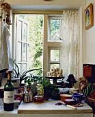 Eine Marmorplatte mit Zwiebel und Öl vor dem Küchenfenster mit weißem Spitzenvorhang