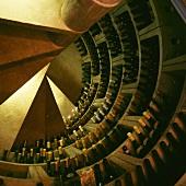 Luftaufnahme einer Wendeltreppe, die zu einem Kellerraum mit kreisförmigen Regalen für Weine führt