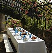 Gedeckter Tisch unter dem Pergola