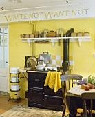Alte gelb getönte Küche mit Tontöpfen auf Konsole über antiken Küchenofen