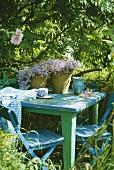 Pflanzentöpfe auf grün und blau lackiertem Gartentisch