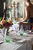 A table laid with green glasses, flowers and candles