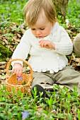Kleines Kind mit Körbchen auf Waldboden sitzend