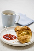 Croissant with strawberry jam and coffee