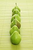 Six pears on a bast mat