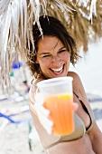 Frau mit Orangensaft unter einem Strohschirm