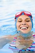 Frau mit Badekappe und Schwimmbrille im Schwimmbecken