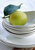 Lemon with leaf in stacked white bowls