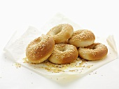 Several sesame bagels on paper