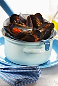 Steamed mussels in a strainer on a pan